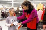 Gov. Sarah Palin presents a gift-card donated by Wal-Mart and The Salvation Army to 7-year-old Charline Fager, Dec. 2007 (Credit: Sgt. Karima Turner, Alaska National Guard Public Affairs)